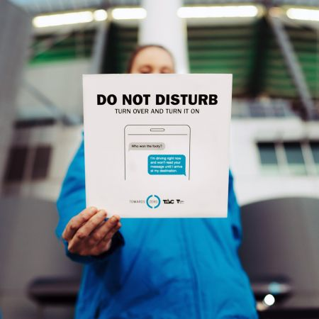 A woman holding a card which includes information on the do not disturb while driving feature