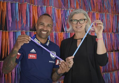 Megan Jacobs and Archie Thompson hold up ribbons with Christmas messages